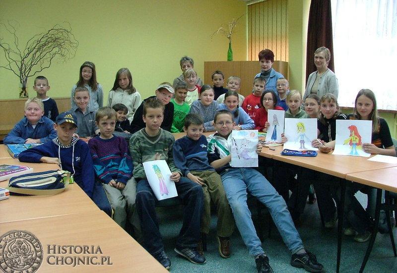 """Pamiątkowa fotografia uczestników i opiekunów zajęć świetlicowych w tzw. """"blaszaku""""."""