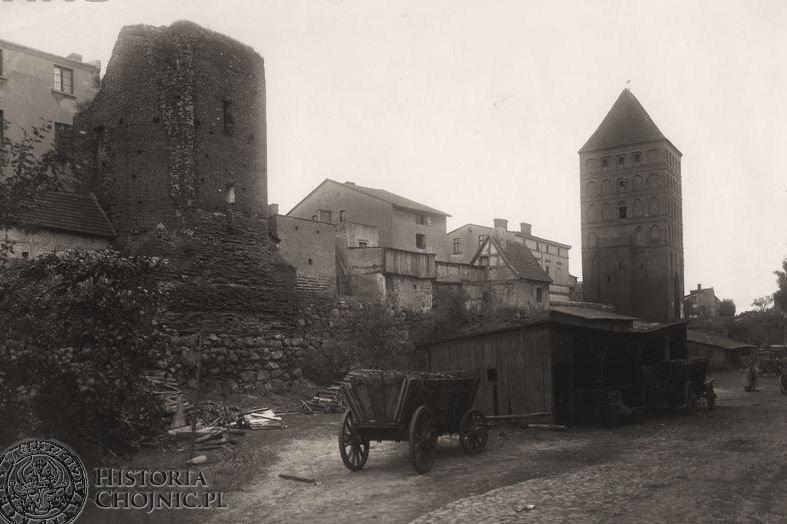 Fragment murów obronnych z bramą Człuchowską. Widoczne wozy wypełnione drewnem.
