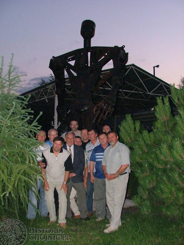 Pamiątkowa fotografia byłych pracowników Chojnickiego Przedsiębiorstwa Budowlanego przy dyskobolu.